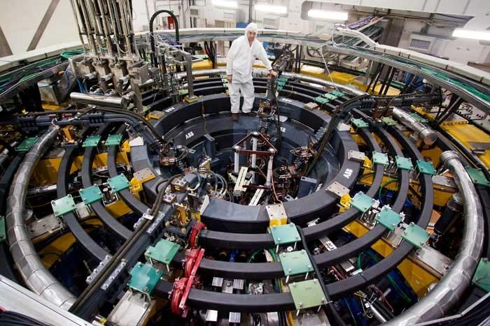 si vedono operatori in tuta asettica che lavorano su un enorme anello di cavi e tubi