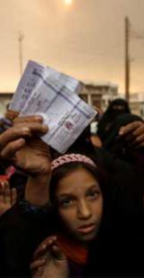 A displaced woman shows her refugee identification paper